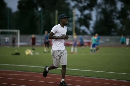 he: African male sportsman in a cap running on stadium track, he trains endurance
