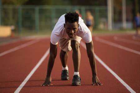 African american male sportsman ready to run on stadium track, sprint run from low start