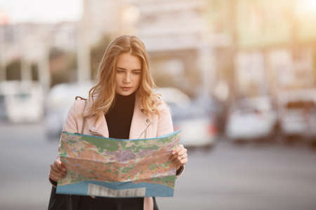 Tourist woman traveller looking to map standing in european city street