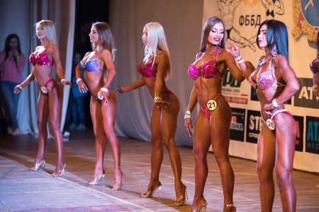UKRAINE, DNEPR - OCTOBER 08, 2017: Miss fitness bikini competition show. Opened championship. Strong musculars athletes women posing on a stage.