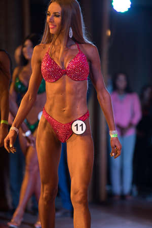 UKRAINE, DNEPR - OCTOBER 08, 2017: Miss bikini competition show. Opened championship. Strong musculars athlete woman posing on a stage.
