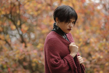 Unconventional woman portrait in marsala color cardigan with black leather sword belt