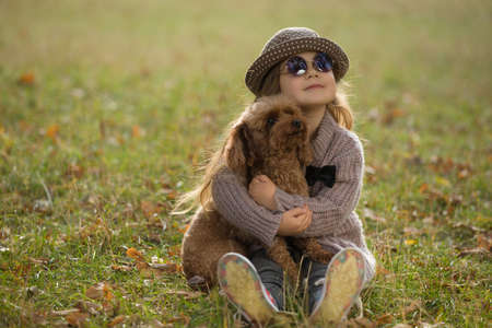 Little girl in hat sitting on grass hugging dog together at the autumn meadow, art portrait Stock Photo