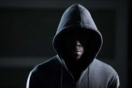 Mysterious african man with hood in darkness