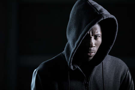 Angry gangster african man in hood, darkness