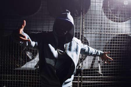 Com rapper moderno dançando na garagem. Estilo de vida urbano, hip hop. Foto de archivo