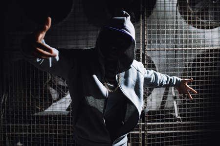 Modern rapper dancing in garage. Urban lifestyle, hip hop.