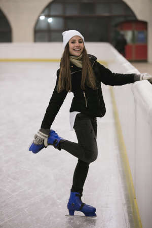 Young woman standing on ice of a skating rink fastens her skates