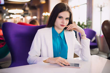 Strict business woman sitting at table in a futuristic cafe