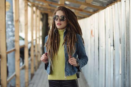 Stylish woman with dreadlocks, fashion portrait in city