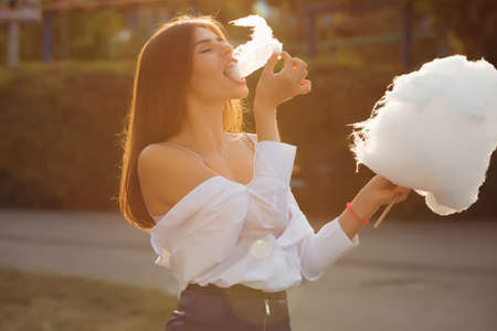Happy woman eating cotton candy in a park Stock Photo