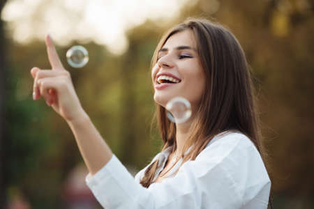 Happy girl catches soap bubbles