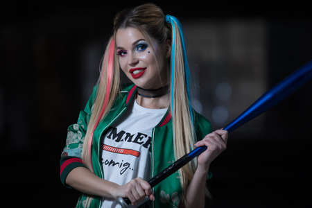 Unusual woman holding baseball-bat with fantastic costume and makeup 免版税图像