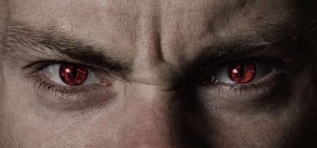 Gros plan sur les yeux du diable en colère rouge Banque d'images