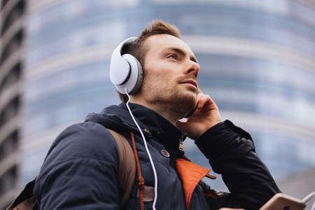 Homme au casque écoutant de la musique à l'extérieur en ville