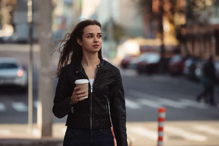 Beautiful woman holding paper coffee cup and enjoying a walk in the city