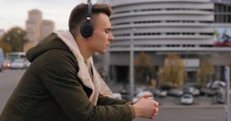 Young man listening to music in headphones at city bridge and thinking