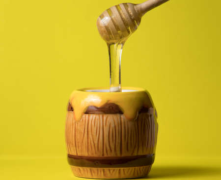 Honey pouring into bowl close-up, yellow background. Healthy natural sweet dessert.