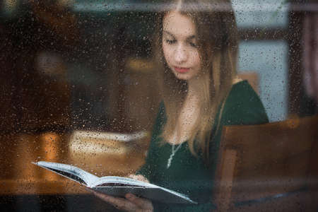 Woman reading book in the cafe, view through wet window at rainy day Stockfoto