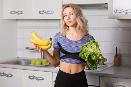 Portrait of woman holding bananas and salad on kitchen, healthy food concept Reklamní fotografie