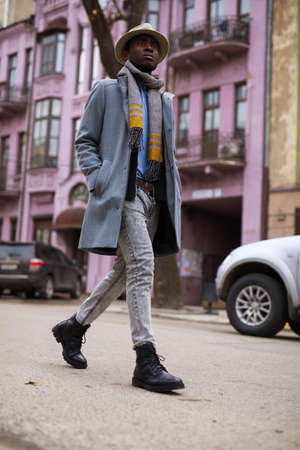 Fashion model african american man in coat and hat walking along city street Reklamní fotografie - 118483548