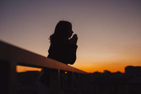 Silhouette of woman thinks and dreams about future at sunset in city Banco de Imagens