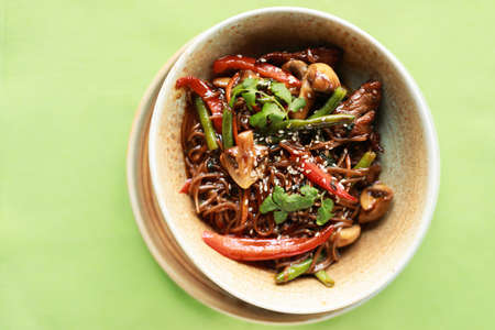 Buckwheat soba with veal, vegetables and mushrooms, top view, green background