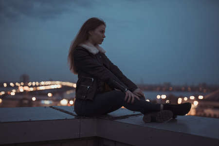 Silhouette of alone woman sitting on the roof, evening sky background, city scape