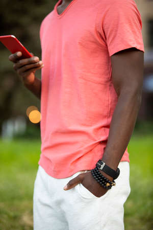 Unrecognizable African american man in living coral t-shirt using smartphone send the message Stok Fotoğraf