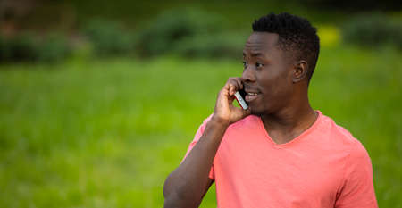 African american man in living coral t-shirt talking by smartphone at summer day