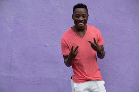 African American man model posing in empty living coral color t-shirt standing against violet wall background showing cool gesture Stok Fotoğraf