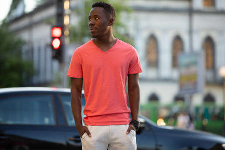 African american man in living coral t-shirt walking at city street, casual style, crossing a road Stok Fotoğraf