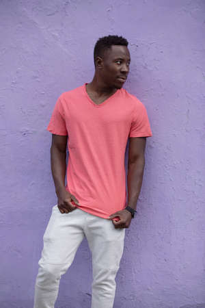 African American man model posing in empty living coral color t-shirt standing against violet wall background