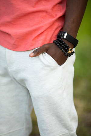 Stylish guy with hand in pocket in living coral t-shirt, cropped shot Stok Fotoğraf