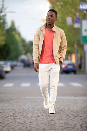 African american man in living coral t-shirt walking at city street, casual style
