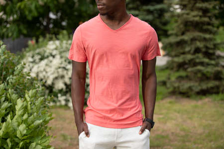 Unrecognizable African American man in living coral color empty t-shirt standing near bush outdoor, mockup Stok Fotoğraf