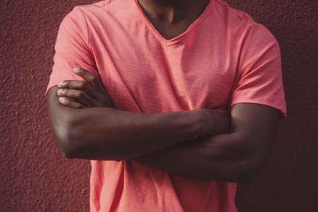 Crossed arms of the African man in living coral t-shirt