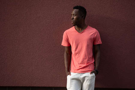 African American man model posing in empty living coral color t-shirt