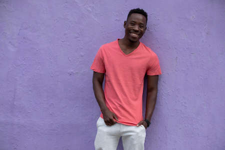 Smiling African American man model posing in empty living coral color t-shirt standing against violet wall background Stok Fotoğraf