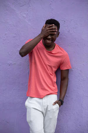 Smiling laughing African American man model posing in empty living coral color t-shirt standing against violet wall background Stok Fotoğraf