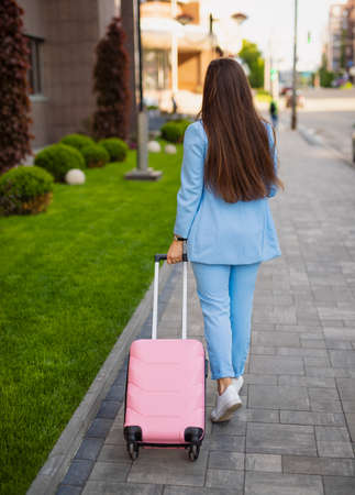 Unrecognizable businesswoman rolls a suitcase in city, back view