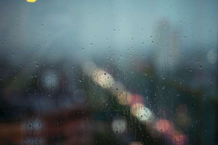 Window with raindrops, city on background