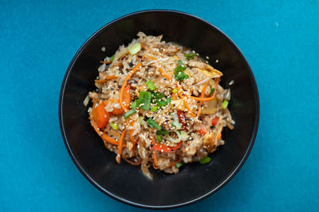 Plate with asian food, rice with vegetables and sesame, blue background