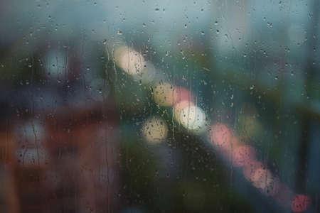 Raindrops, rain behind the window, city on background