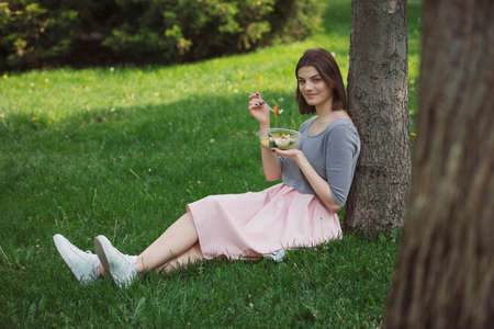 Woman eating fresh salad sitting at summer park leaning on tree trunk, healthy food concept Stok Fotoğraf