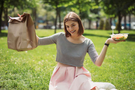 Woman holding and demonstrating fresh salad sitting at summer park, healthy food concept, empty blank paper bag
