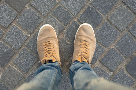 POV of male gumshoes on paving slabs, view from above