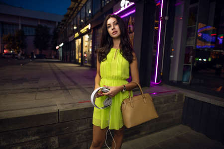 Beautiful woman in dress standing at night city, art portrait, holding bag and headphone