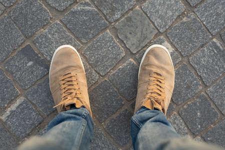 POV męskich butów gumowych na płytach chodnikowych, widok z góry