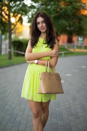 Beautiful lady portrait standing in a summer city holding bag